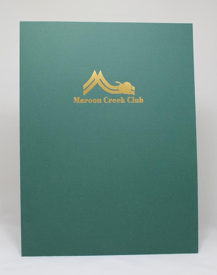 Presentation folder on green linen, gold foil